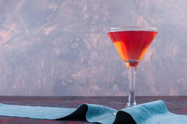 Une tasse en verre de jus de fruits posée sur une nappe.