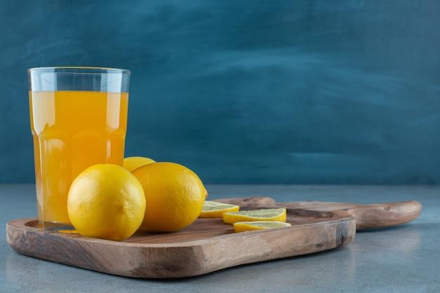 Une tasse en verre de jus d'orange avec des citrons frais.