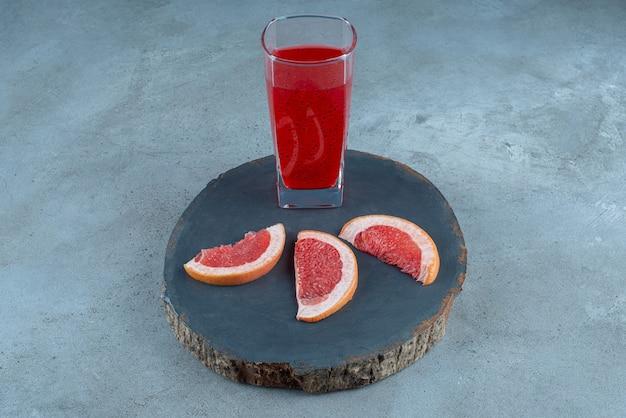 Une tasse en verre de jus rouge avec des tranches de pamplemousse.