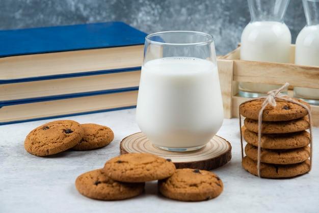 Une tasse en verre de lait savoureux avec des biscuits et des livres.