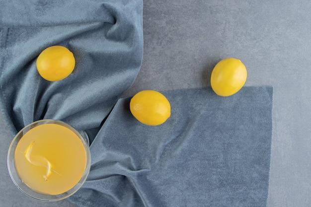 Une tasse en verre de limonade avec des citrons entiers