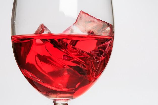 Tasse en verre avec liquide rouge et glace