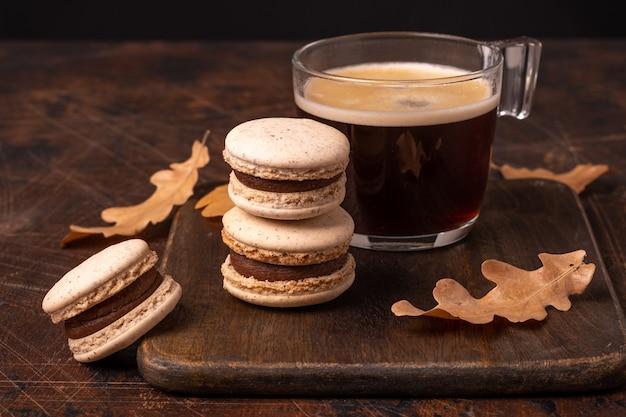 Tasse en verre de macarons au café et au chocolat sur fond de bois. composition d'automne confortable - image