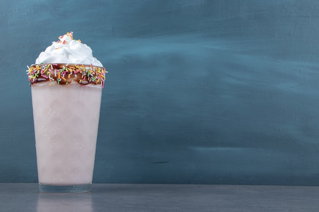 Une tasse en verre de milkshake sucré avec de la crème fouettée