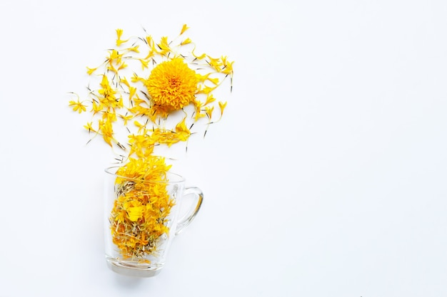 Une tasse en verre avec des pétales de fleurs de souci. concept de tisane de fleurs.