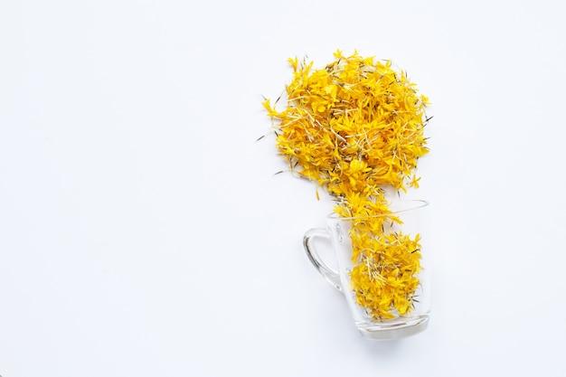Une tasse en verre avec des pétales de fleurs de souci sur fond blanc. concept de tisane de fleurs.