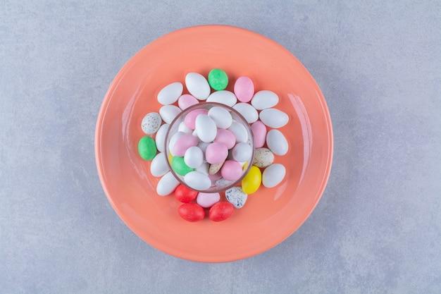 Une tasse en verre pleine de bonbons aux haricots colorés sur une surface grise.photo de haute qualité