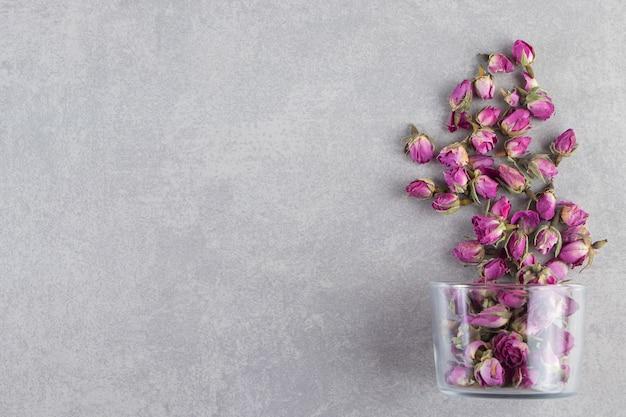 Une tasse en verre pleine de boutons de fleurs roses séchées placées sur fond de pierre.