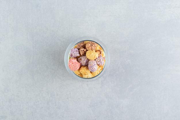Une tasse en verre pleine de pop-corn multicolore sucré.