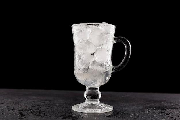 Une tasse en verre remplie de glace jusqu'au dessus est posée sur un comptoir en pierre humide.
