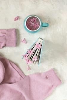 Tasse avec un verre, des signets de fleurs fraîches dans un livre ouvert, pull rose en laine sur une table lumineuse, vue du dessus
