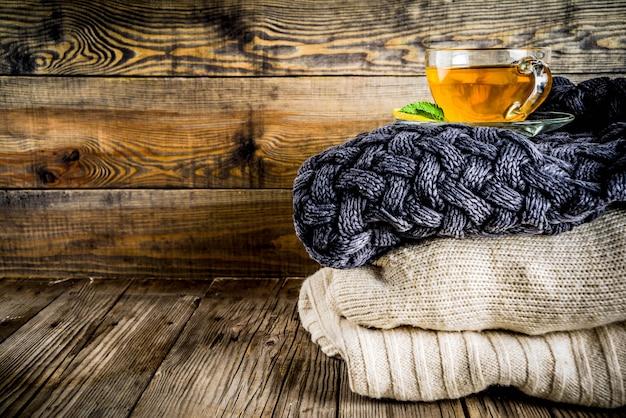 Tasse en verre de thé au citron, menthe et épices, sur une vieille table en bois rustique avec des couvertures chaudes.