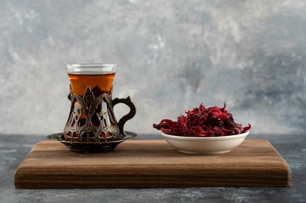Une tasse en verre de thé chaud avec des fleurs séchées sur une planche à découper en bois.