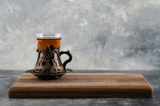 Une tasse en verre de thé chaud sur une planche à découper en bois.