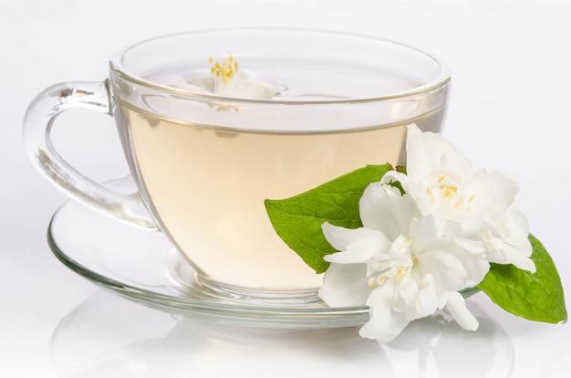 Tasse en verre de thé avec des fleurs et des feuilles de jasmin