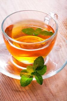 Tasse en verre de thé à la menthe sur table en bois