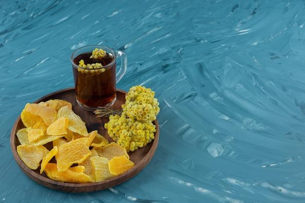 Une tasse en verre de thé noir avec des fruits secs placés sur une planche ronde.