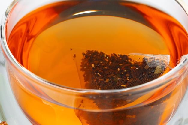 Tasse en verre de thé noir se bouchent