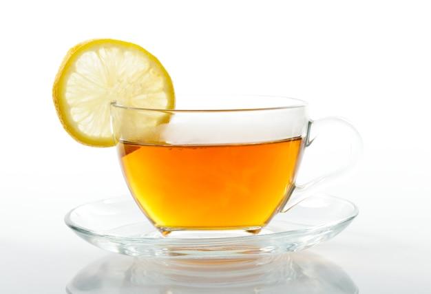 Tasse en verre de thé noir avec une tranche de citron isolé sur blanc