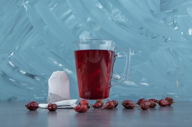 Une tasse en verre de thé de rose musquée sur du marbre.