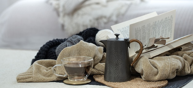 Tasse en verre de thé, théière et livre sur un espace flou léger aux couleurs froides.