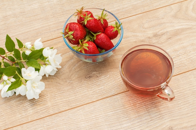 Tasse en verre de thé vert, bol avec fraises fraîches et fleurs de jasmin blanc sur fond en bois. vue de dessus.