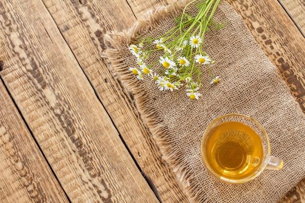 Tasse en verre de thé vert et de fleurs de camomille blanches fraîches sur un sac et un fond en bois ancien. vue de dessus.