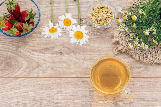 Tasse en verre de thé vert, fleurs de camomille, bols en verre avec fleurs sèches de matricaria chamomilla et fraises fraîches sur les planches en bois. vue de dessus.