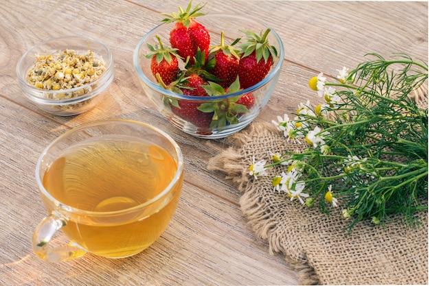 Tasse en verre de thé vert, fleurs de camomille, bols en verre avec fleurs sèches de matricaria chamomilla et fraises fraîches sur les planches en bois.