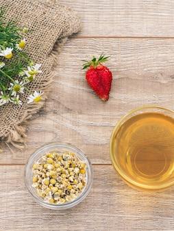 Tasse en verre de thé vert, fleurs de camomille fraîches, fraise et un petit bol en verre avec des fleurs sèches de matricaria chamomilla sur le fond en bois. vue de dessus.