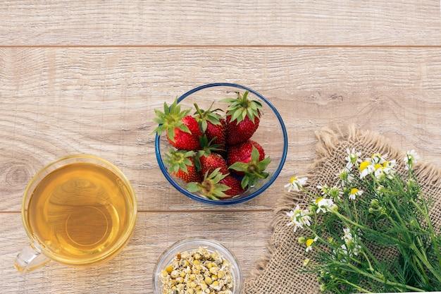 Tasse en verre de thé vert, fleurs de camomille fraîches et sèches, fraises dans un bol sur les planches de bois. vue de dessus.