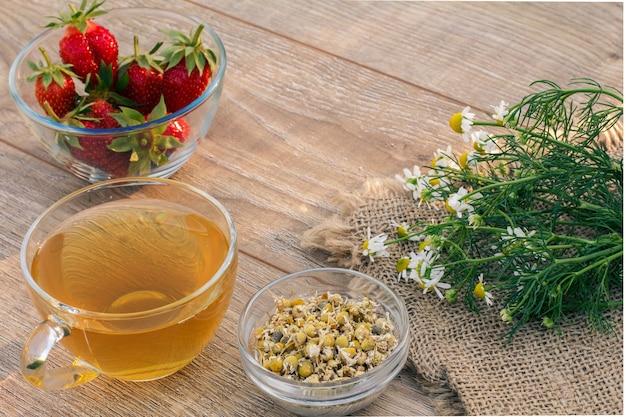 Tasse en verre de thé vert, fleurs de camomille sur un sac, bols en verre avec des fleurs sèches de matricaria chamomilla et des fraises fraîches sur les planches de bois.