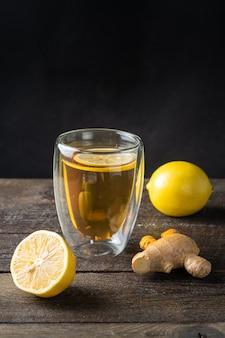 Une tasse en verre de thé vert naturel au gingembre, citron, menthe et miel sur bois rustique