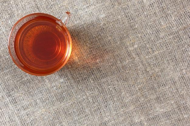 Tasse en verre transparent avec du thé noir sur une nappe de toile de jute rugueuse, vue de dessus.