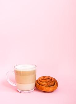 Tasse en verre transparent de latte de café chaud sur et petit pain de cannelle doux sur le fond rose