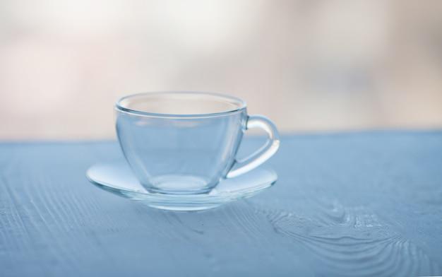 Tasse en verre vide sur table en bois.