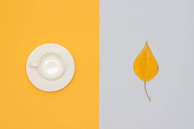 Tasse vide blanche avec soucoupe et feuille d'automne