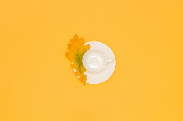 Tasse vide blanche avec soucoupe et feuille de chêne d'automne au centre jaune.