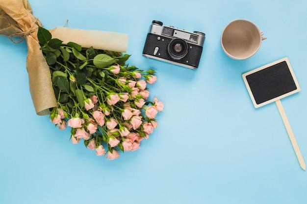 Tasse vide; caméra; bouquet de roses roses et étiquette vierge sur fond bleu