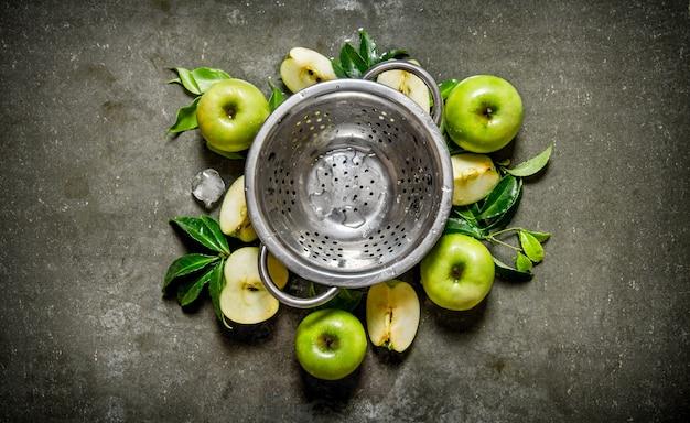 Tasse vide et pommes vertes avec des feuilles. sur une table en pierre rustique. vue de dessus