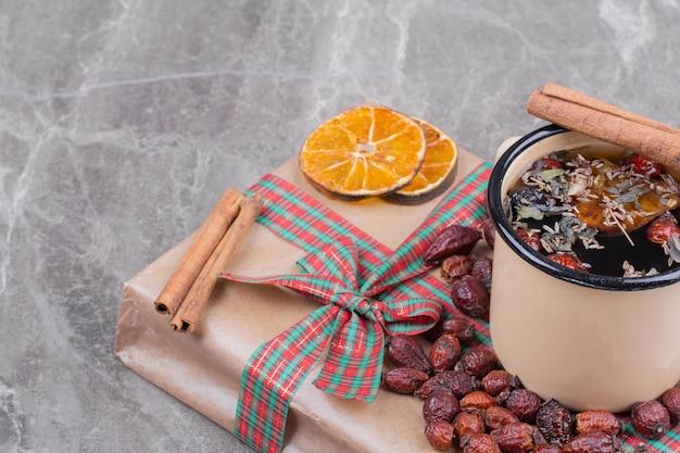 Une tasse de vin brillant sur une boîte cadeau avec des herbes et des épices