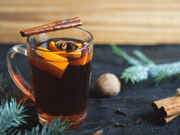 Tasse de vin chaud à la cannelle et aux épices sur une table en bois avec des branches du sapin de noël