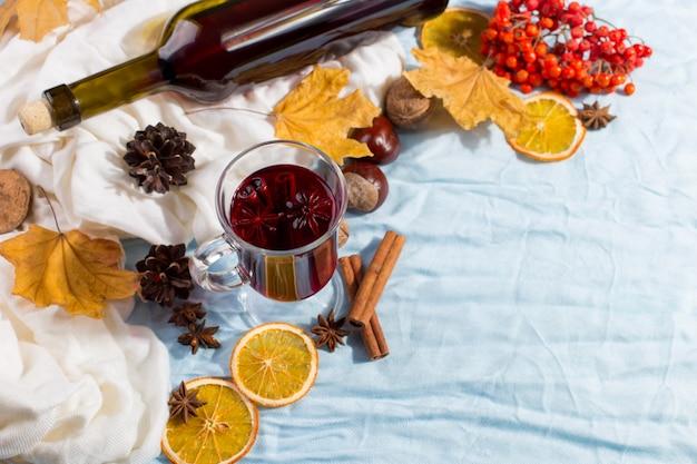 Une tasse de vin chaud avec des épices, une bouteille, des feuilles sèches et des oranges sur la table. humeur d'automne, méthode pour rester au chaud dans le froid, fond, lumière du matin.