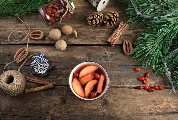 Une tasse de vin chaud avec des fruits, des baies et de la cannelle sur un fond en bois.