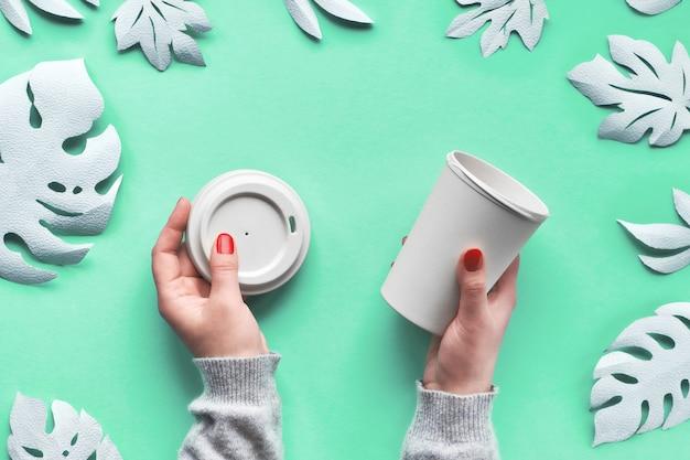 Tasse de voyage café réutilisable élégante, tasse en bambou avec couvercle dans les mains. papier aqua menthe bleu menthe avec des feuilles exotiques d'artisanat en papier blanc. tendance mode de vie écologique zéro déchet.