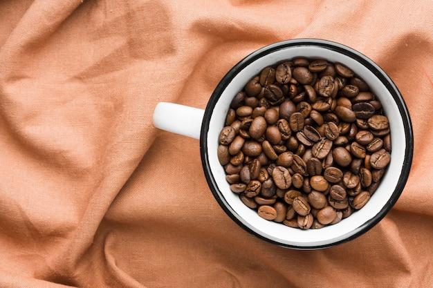 Tasse vue de dessus avec grains de café torréfiés