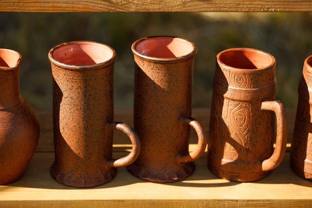 Des tasses en argile brune se tiennent en rangées sur une étagère en bois.