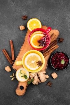Tasses avec arôme de fruits de thé sur planche de bois