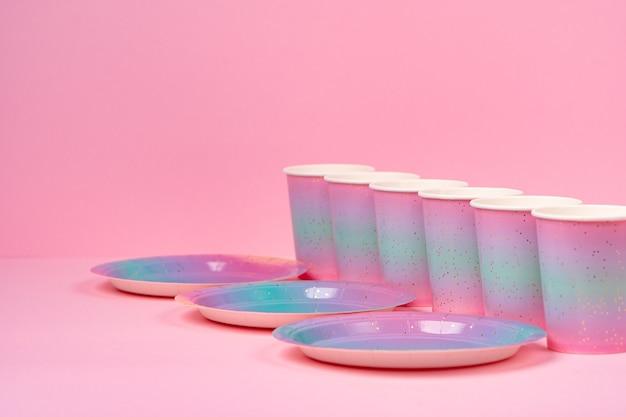 Tasses et assiettes de fête rose sur fond rose