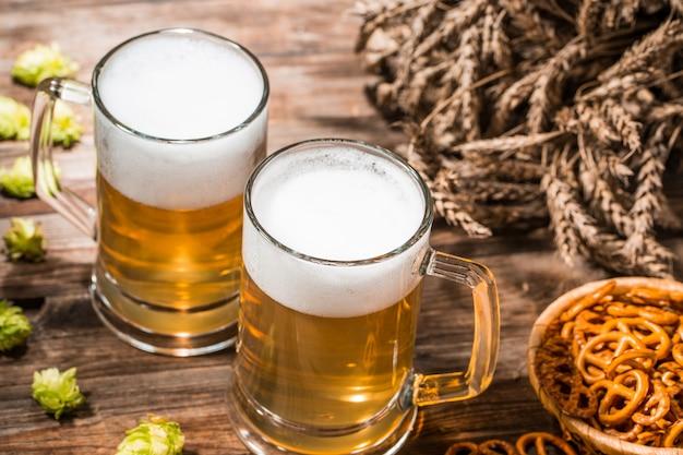 Tasses à bière mousseuse, houblon, bretzels et blé, vue de dessus